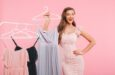photo-joyful-young-woman-20s-smiling-posing-near-rack-with-lots-dresses-hangers-isolated-pink-wall_171337-36831